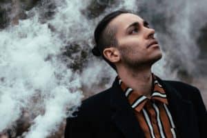 Mann steht vor einer Rauchwolke und schaut hoch