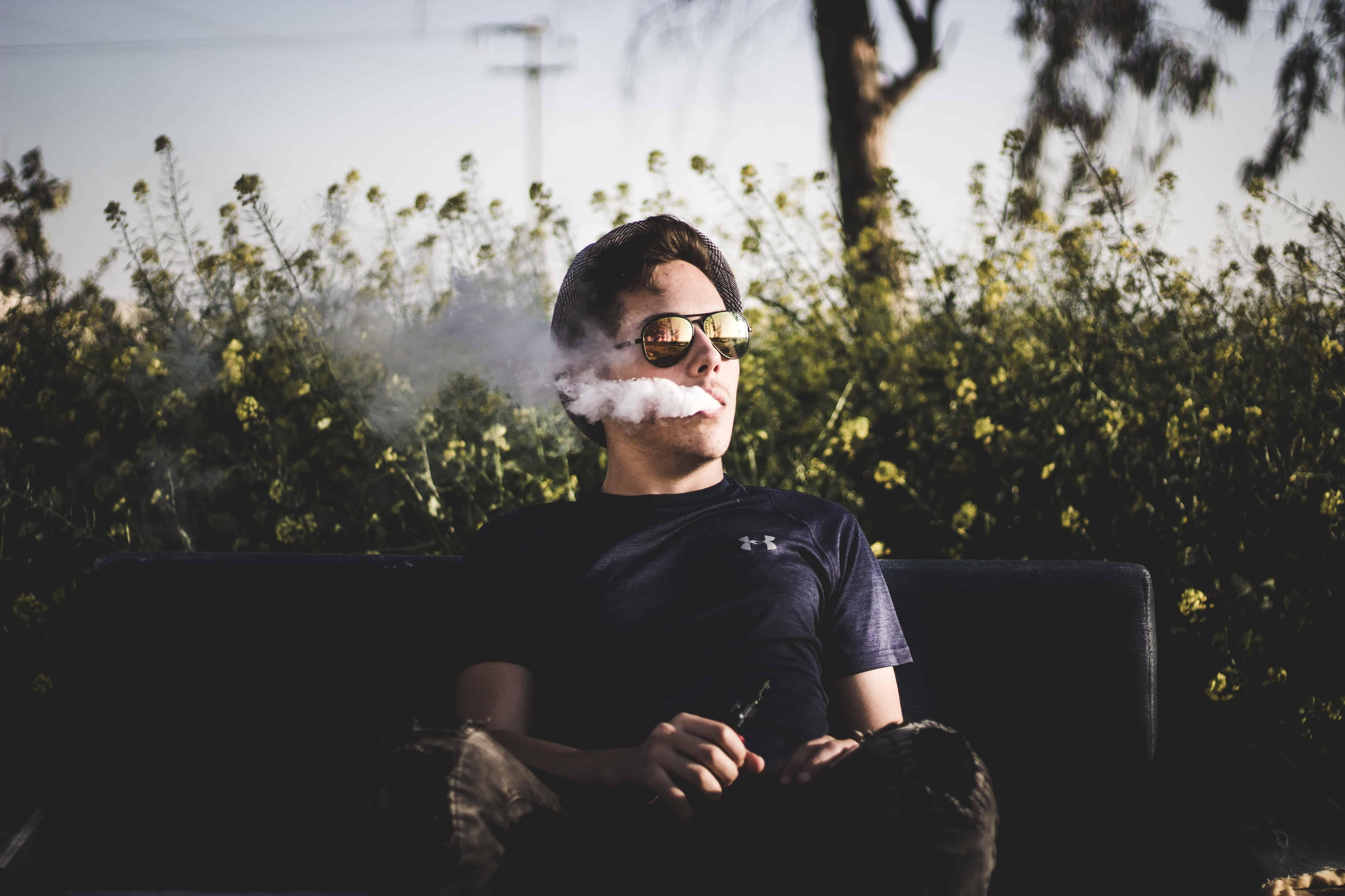 Mann auf Bank raucht
