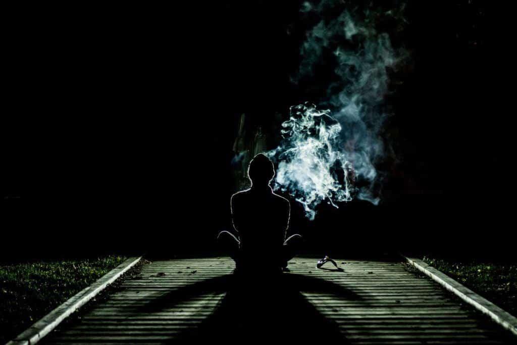 Person raucht auf Gleise
