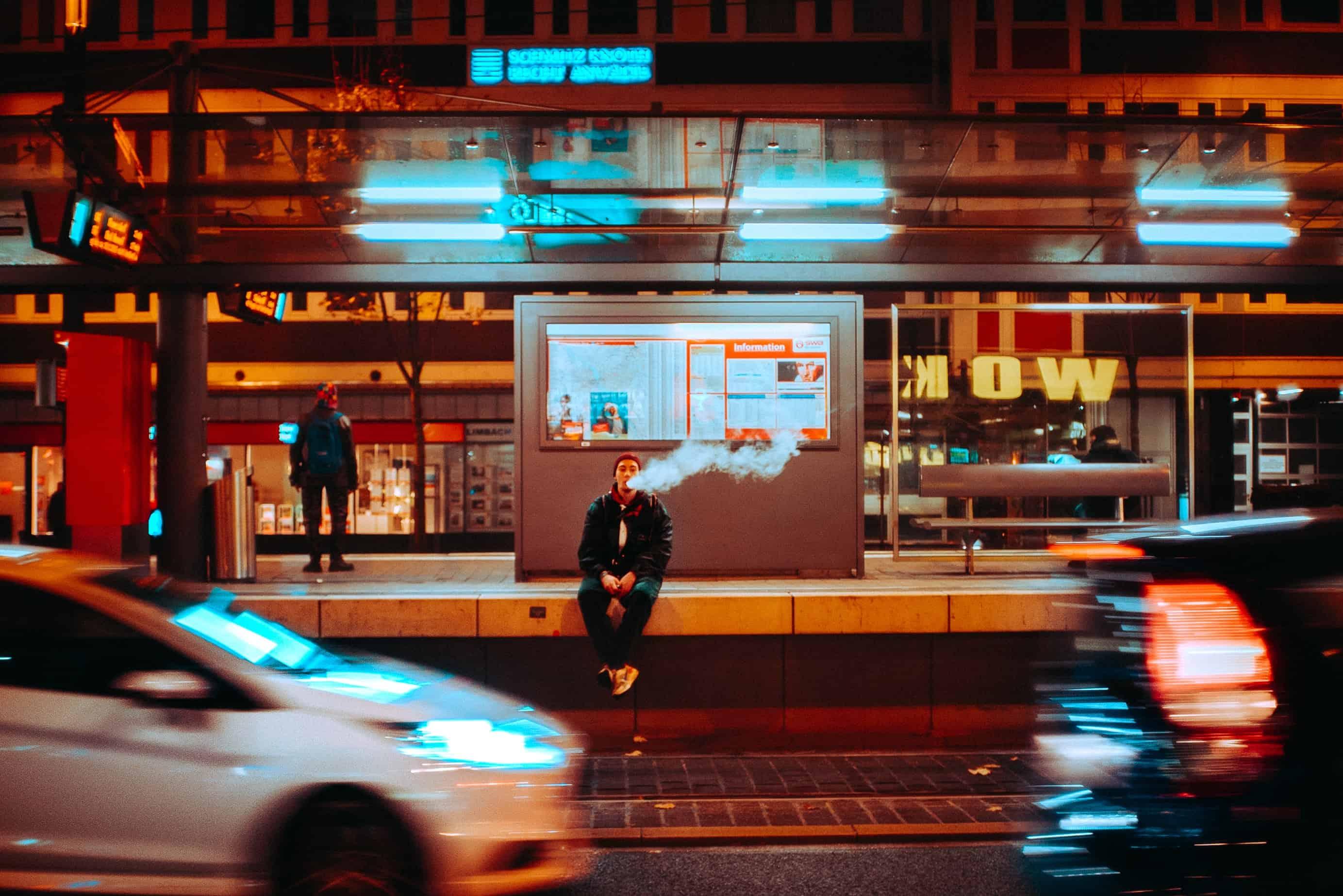 Junge raucht E Zigarette an einer Bushaltestelle, Straße