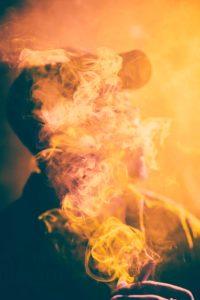 Mann mit E Zigarette voller Rauch im Gesicht