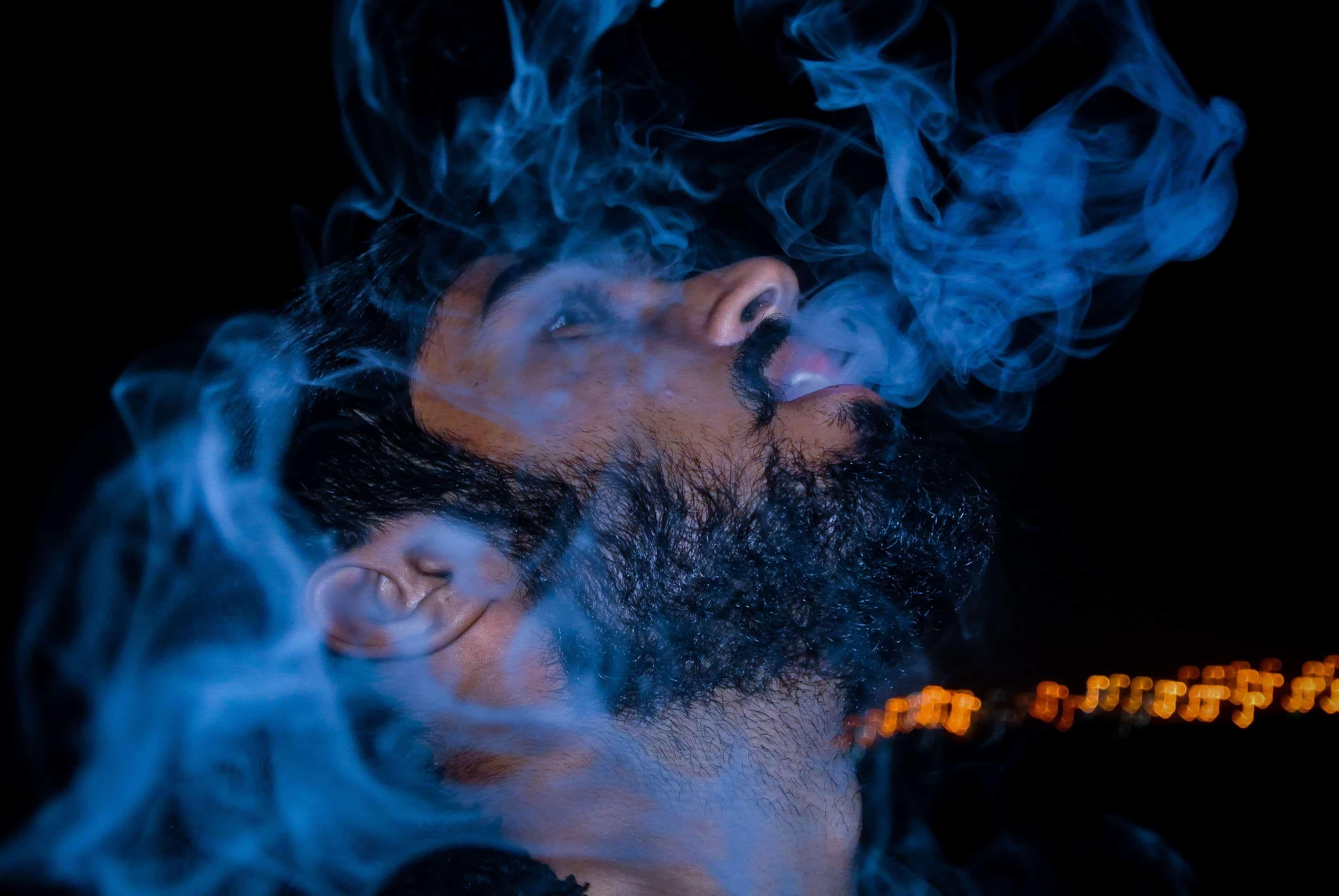 Mann mit schwarzem Shirt und blauem Rauch