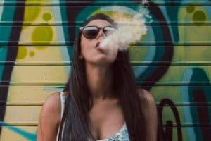 Frau raucht Garage im Hintergrund