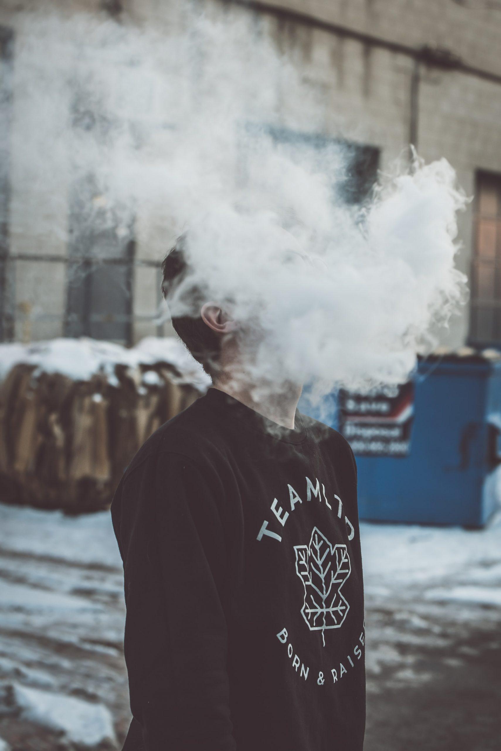 Mann mit großer Rauchwolke durch E-Zigarette in schwarzem Sweatshirt