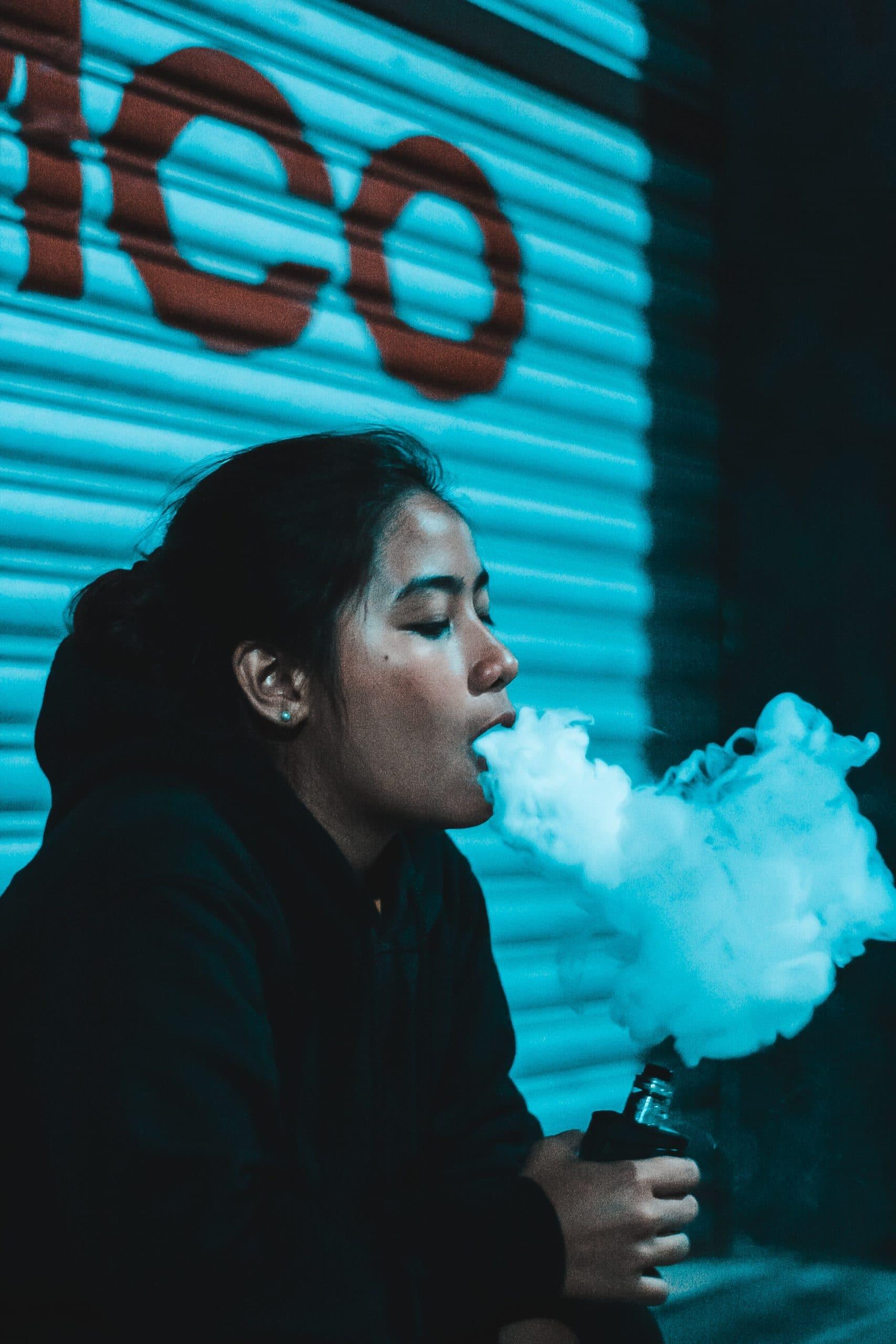 Mädchen mit E zigarette in Hand raucht
