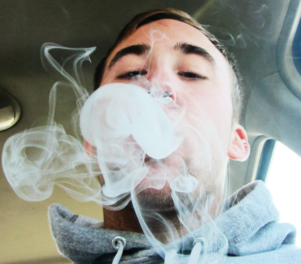 Mann mit grauem Pullover atmet Rauch aus