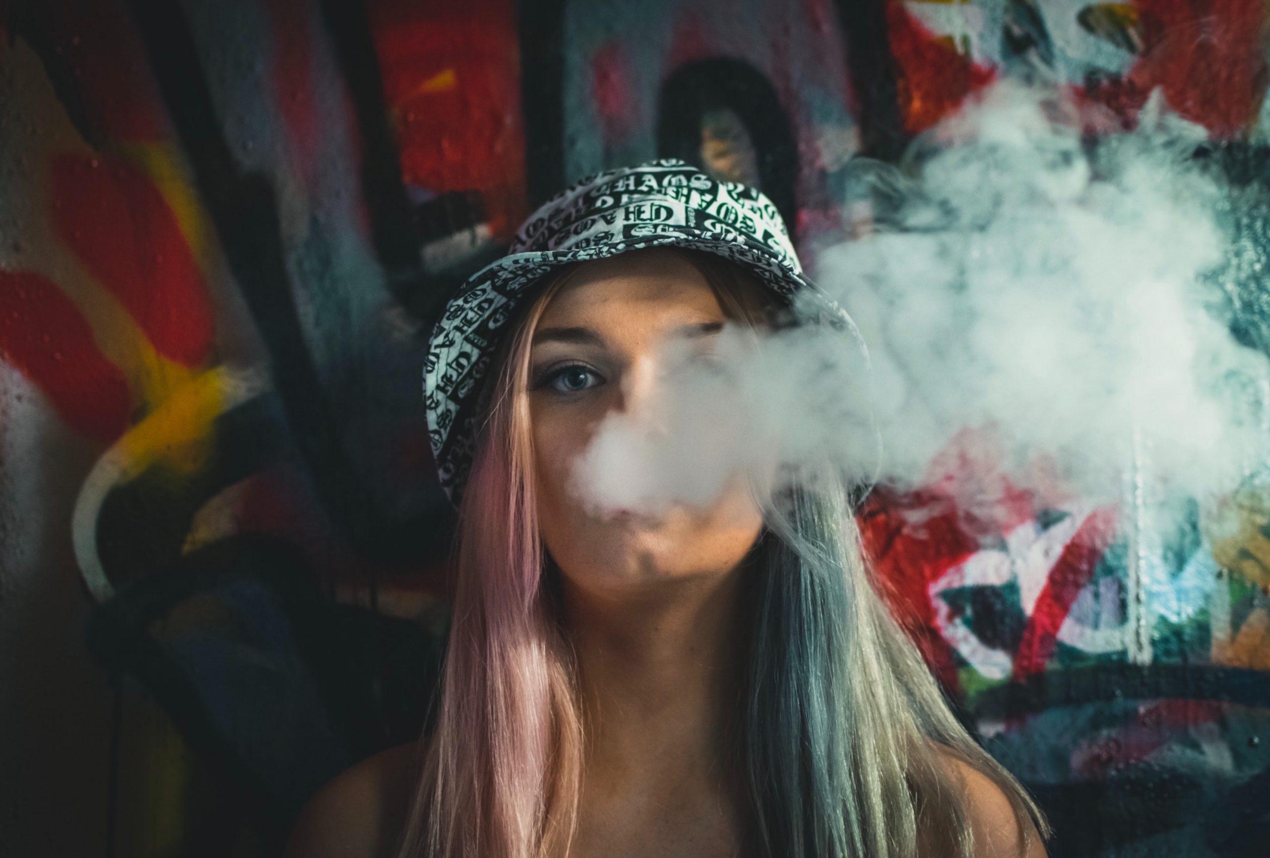 Mädchen mit Mütze am rauchen