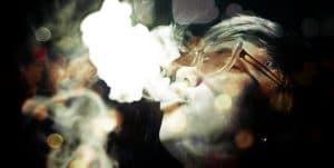 Mann mit Brille und Rauchwolke im Gesicht