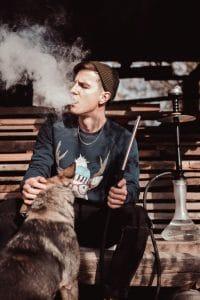 Mann raucht Shisha während er einen Hund streichelt