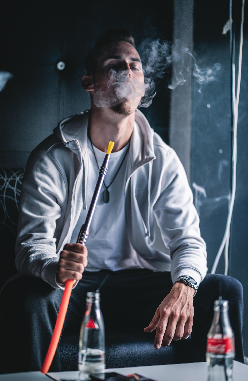 Mann sitzt und raucht Shisha und hat Rauchwolke im Gesicht