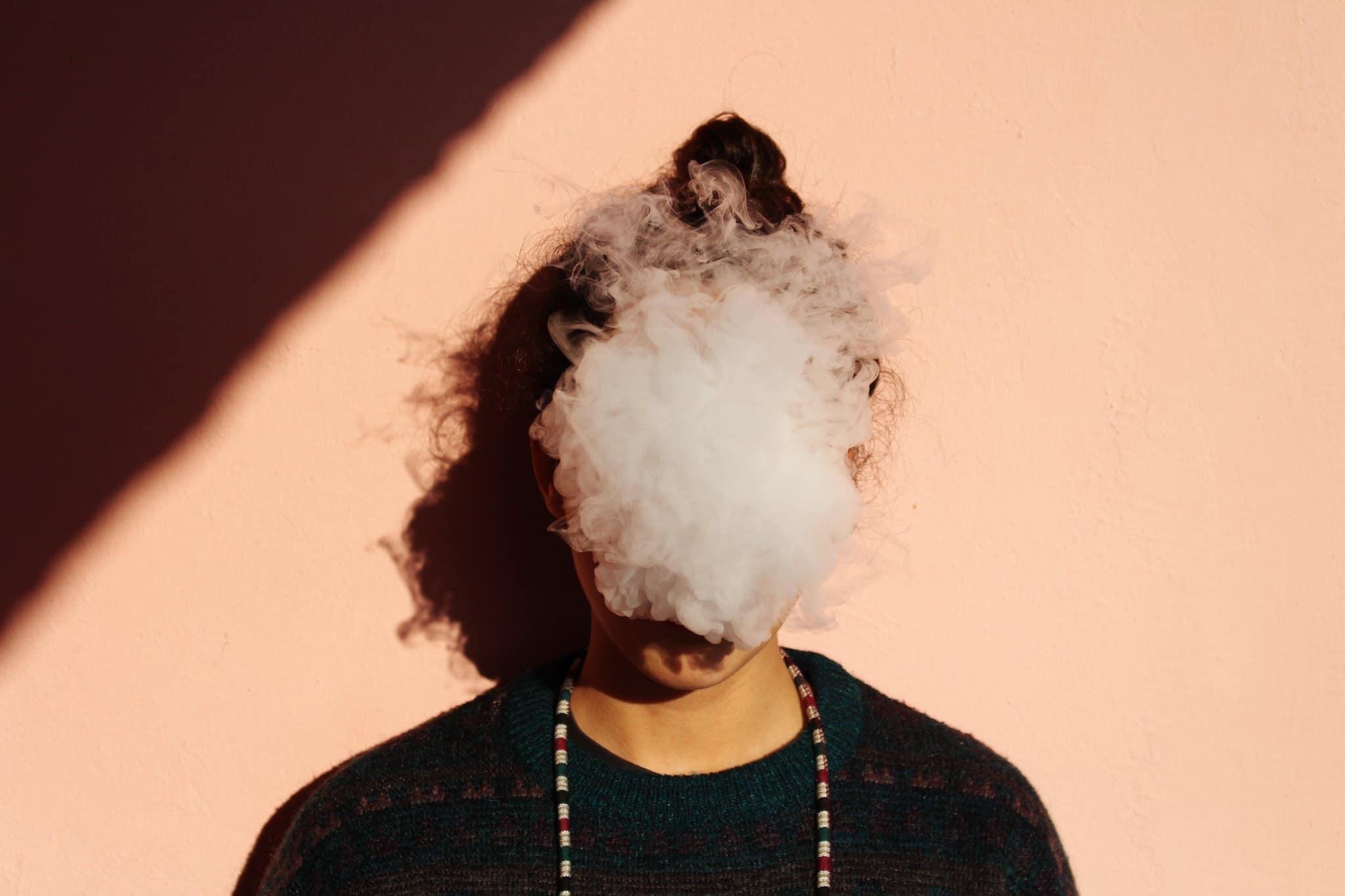 Rauchwolke im Gesicht eines jungen Mannes